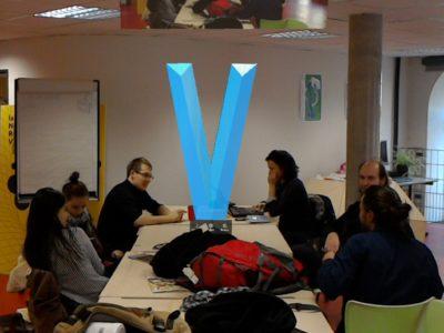 Un V majuscule flotte sur une table au milieu d'un groupe de travail