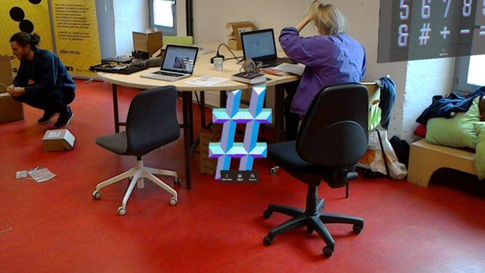 Un dièse flotte dans l'air devant une personne qui travaille à son ordinateur