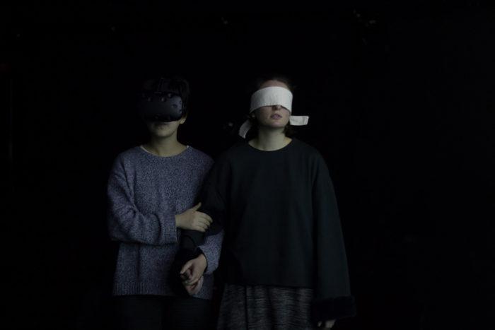 Une personne portant le casque VR, l'autre les yeux bandés