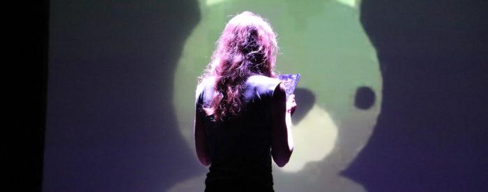 Une femme lit son texte devant l'écran de Vanishing Walks