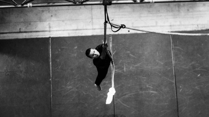 Un artiste circassien en train de grimper à une corde