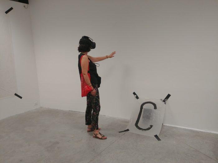 Une femme équipée d'un casque de réalité virtuelle tend le bras vers le mur blanc