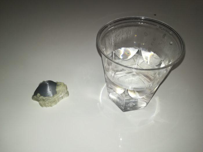 L'objet en 3D à côté d'un verre d'eau