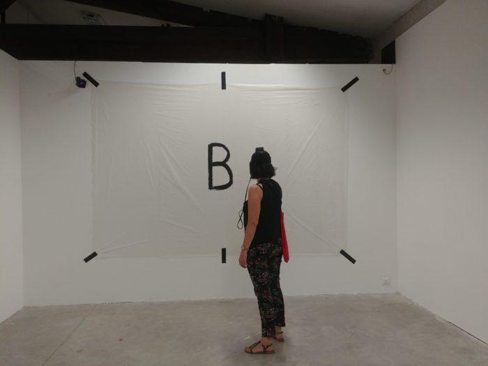 Une femme devant un mur blanc marqué d'un B