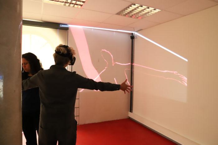 Annie Abrahams avec un casque de VR dans une pièce blanche