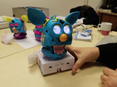 Un Furby aux yeux allumés se tient sur un robot Thymio