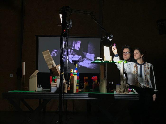 Deux comédiens s'activent autour d'une maquette de ville