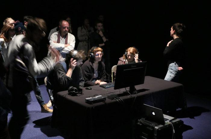 Du public derrière un écran d'ordinateur sur scène