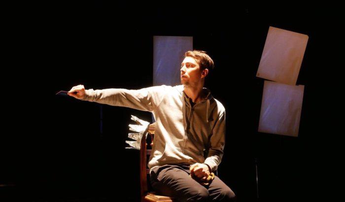 Un comédien assis tend une carte