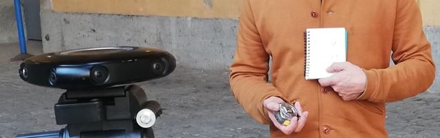 A côté de la caméra, un homme tient un carnet blanc