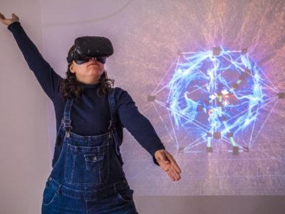 Ariane fait un mouvement des bras avec le casque de réalité virtuelle