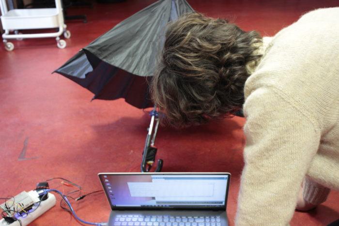 Une personne agenouillée devant un parapluie à demi replié