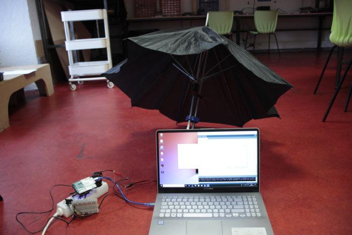 Un parapluie ouvert derrière un ordinateur portable