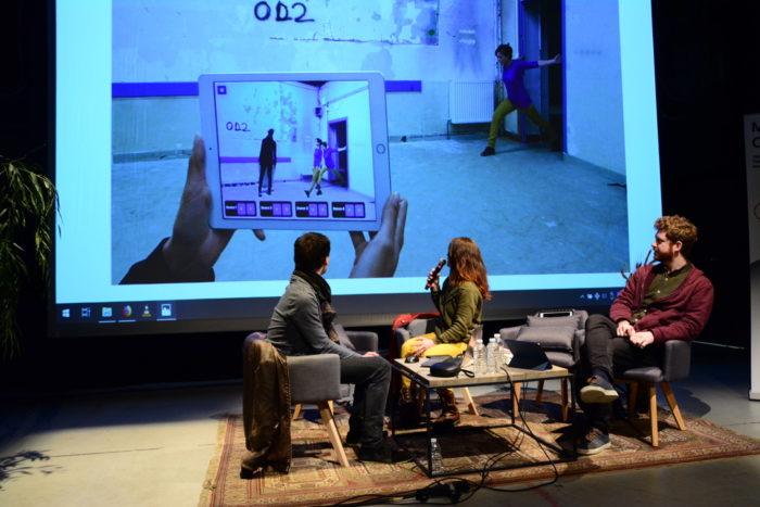 Trois intervenants assis devant un écran