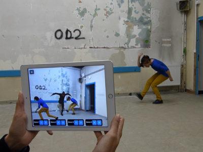 Une danseuse évolue en arrière plan tandis qu'une personne l'observe à travers un écran de tablette tactile