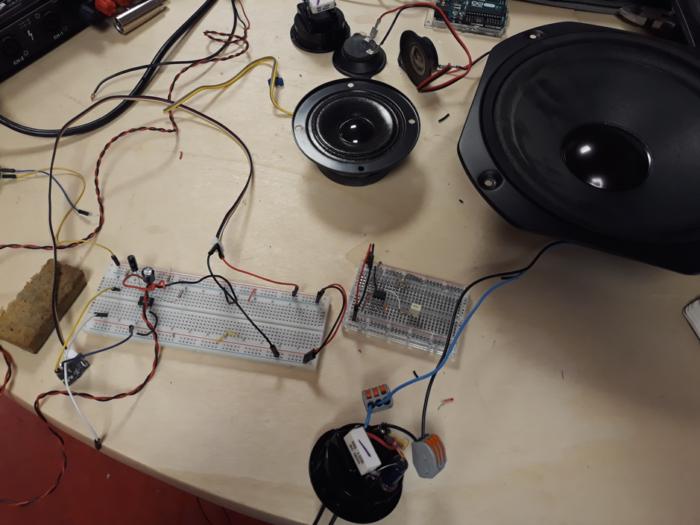 Sur une table, une enceinte avec du matériel électronique