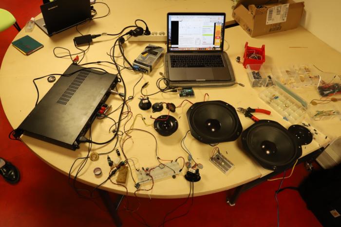 Sur un bureau, des enceintes, un ordinateur, des éléments électroniques