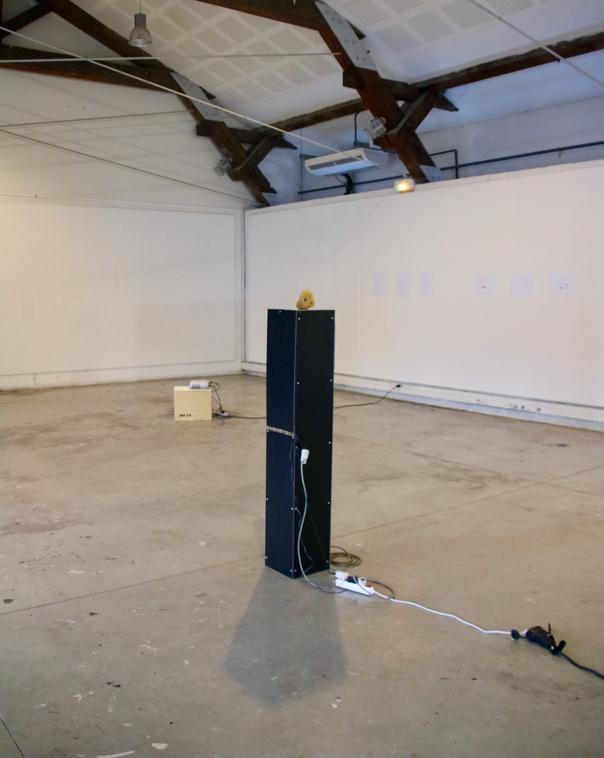 Dans une grande salle vide, la sculpture : une éponde sur un haut socle en métal