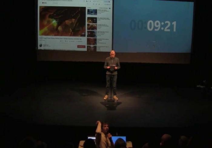 Benjamin seul sur scène devant un écran projeté