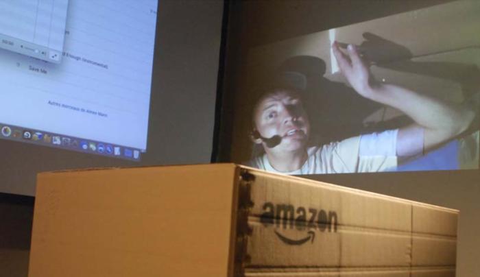 Au premier plan, un carton de livraison Amazon ; à l'arrière-plan Benjamin équipé d'un micro