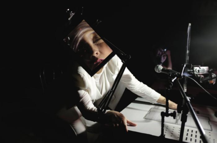 Une femme vêtue de blanc au visage agrandi par un écran