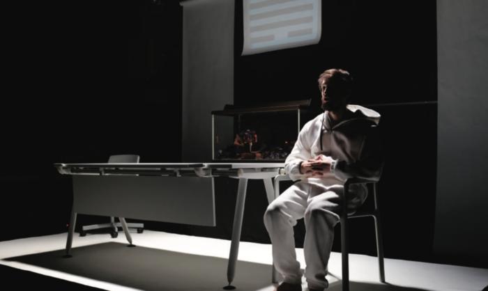 Un homme vêtu de blanc assis au bout d'une table