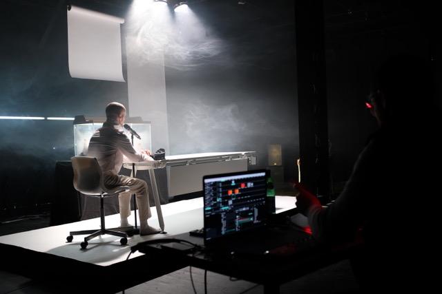 Un homme assis devant un micro, au bout d'une table