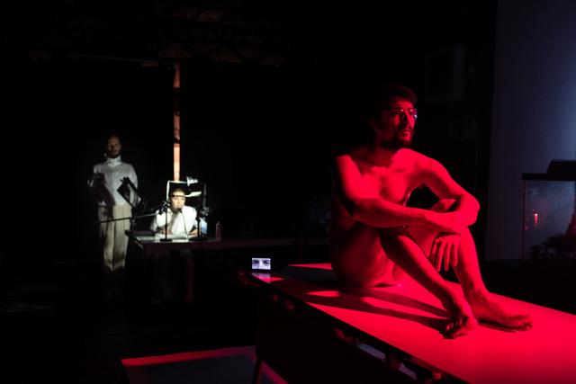 Un homme assis sur une table, éclairé par une lumière rouge