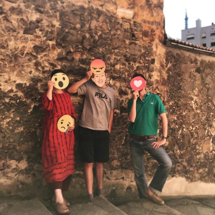 Trois personnes contre un mur, portant des masques emojis