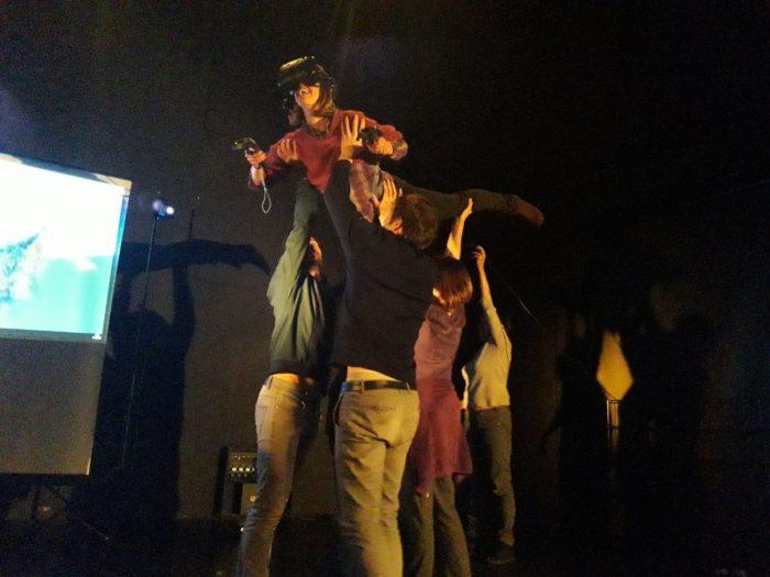 Une personne portant un casque de réalité virtuelle est soulevée dans les airs par d'autres personnes