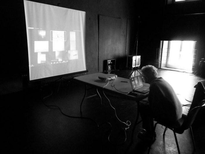 Annie Abrahams assise en bout de table parle à son ordinateur