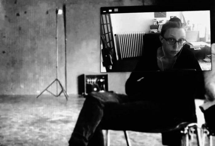 Une personne assise sur une chaise dont le visage apparaît à travers un écran de téléphone